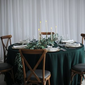 trailing foliage and brass candlestick set table centre