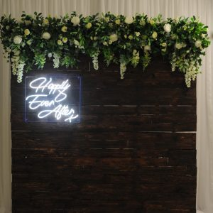 timber floral backdrop with neon sign
